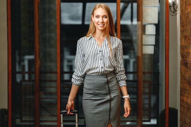 Mulher de negócios atraente em um hotel com uma mala feita, retrato