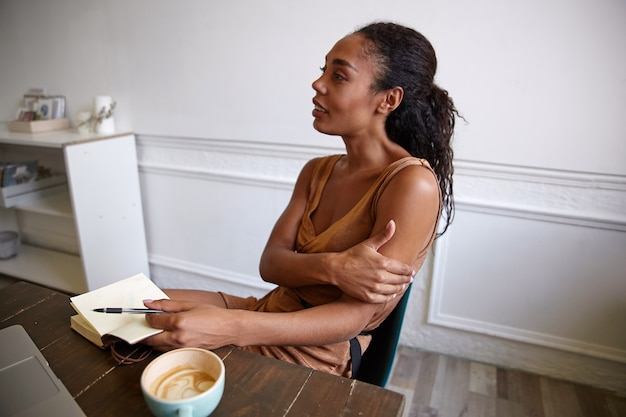 Mulher de negócios atraente em vestido casual sentada à mesa de madeira, entrevistando alguém e fazendo comentários em seu caderno
