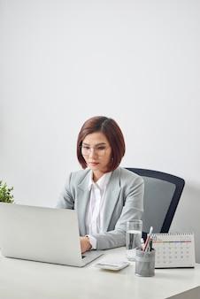 Mulher de negócios atraente está sentada na mesa com o computador e a agenda no escritório