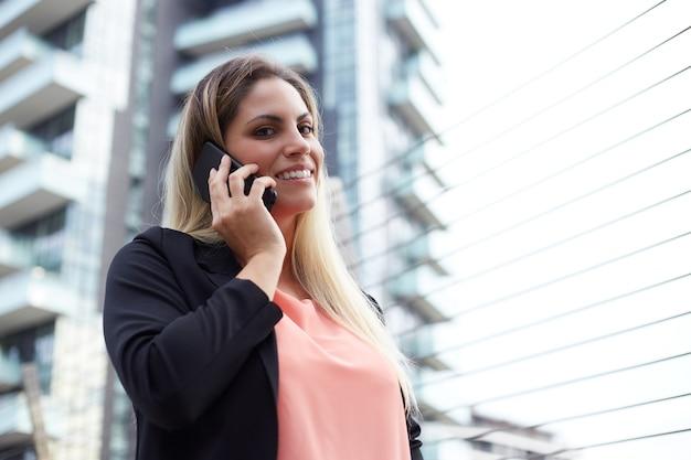 Mulher de negócios atraente falando para celular em ambiente urbano
