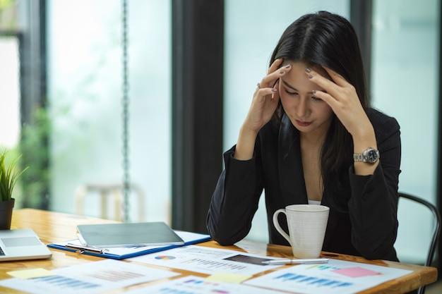 Mulher de negócios atraente ficando estressada com o trabalho com laptop tablet de relatórios financeiros