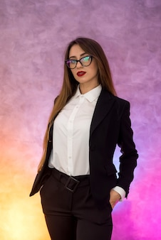 Mulher de negócios atraente gesticulando para uma parede abstrata em óculos originais
