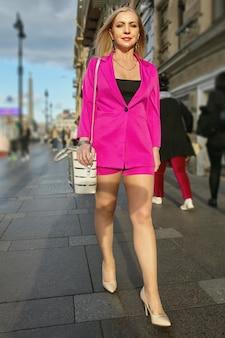 Mulher de negócios atraente madura em terno rosa está andando nas ruas da cidade.