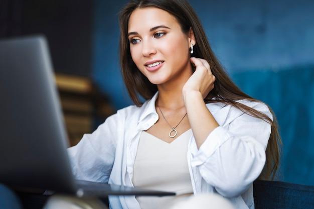 Mulher de negócios atraente se senta à mesa no laptop, smartphone encontra-se na mesa, faz anotações com lápis no caderno.
