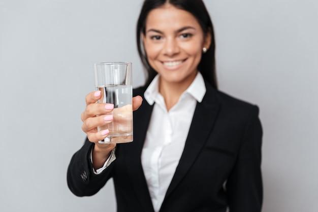 Mulher de negócios atraente sorridente segurando o copo de água mineral