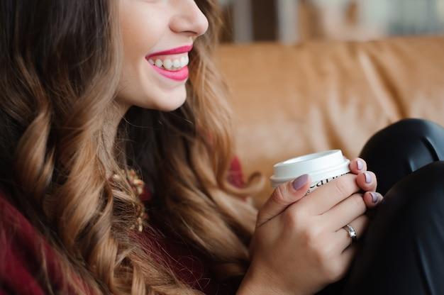 Mulher de negócios atraente tem uma pausa para café no sofá.
