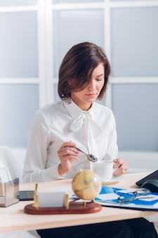 Mulher de negócios atraente tomando café e trabalhando na mesa do escritório