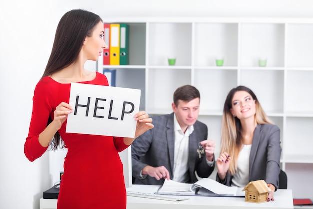 Mulher de negócios atraente, triste e desesperada, sofrendo de estresse na mesa do computador laptop do escritório segurando um cartaz de ajuda