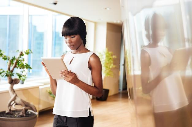 Mulher de negócios atraente usando computador tablet no escritório