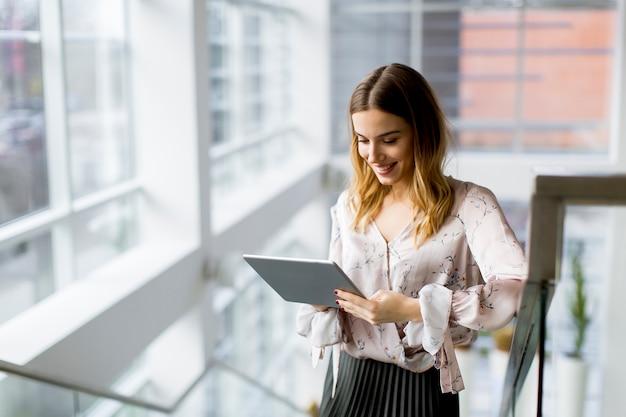 Mulher de negócios atrativa que usa uma tabuleta digital ao estar nas escadas no escritório
