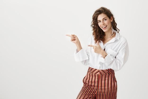 Mulher de negócios atrevida animada apontando o dedo para a esquerda e sorrindo