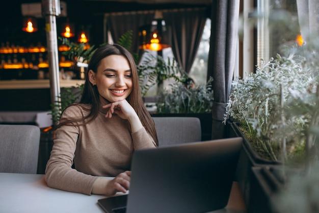 Mulher de negócios, bebendo café e trabalhando no laptop em um café