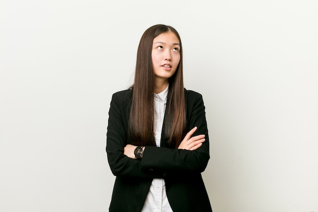 Mulher de negócios bem chinesa jovem cansada de uma tarefa repetitiva.