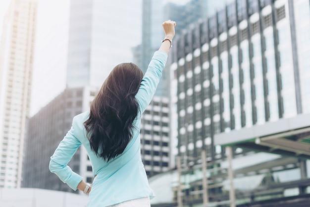 Mulher de negócios bem-sucedida comemorando com os braços erguidos no distrito comercial, conceito de negócios