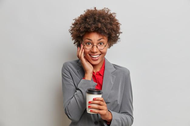 Mulher de negócios bem-sucedida, de aparência agradável e alegre pega um café na cafeteria local, relaxa após um dia de trabalho, sorri positivamente com os dentes brancos, bebe bebida aromática