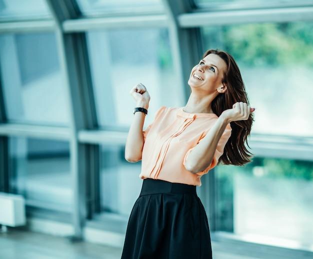 Mulher de negócios bem-sucedida e entusiasmada se alegra com as conquistas em