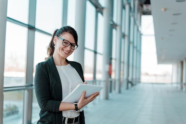 Mulher de negócios bem sucedida e satisfeita, guardando um caderno, olhando a câmera.