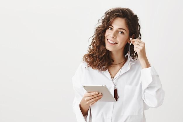 Mulher de negócios bem-sucedida e sorridente coloca o fone de ouvido sem fio e segura o tablet digital