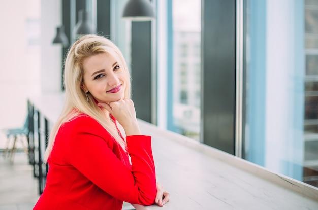 Mulher de negócios bem-sucedida em um terno vermelho em um prédio de escritórios perto da janela