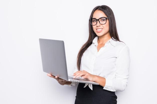 Mulher de negócios bem-sucedida está de pé com o laptop isolado.