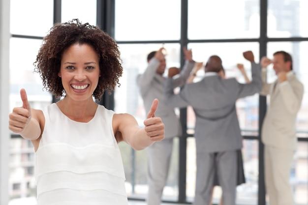 Mulher de negócios bem sucedida fazendo um thum-up com seus colegas