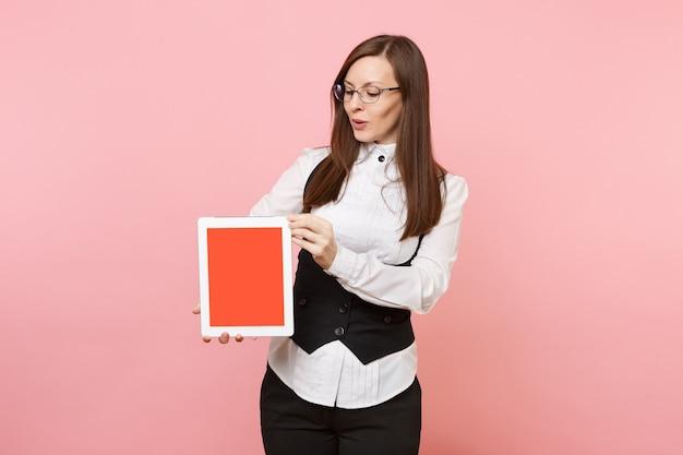 Mulher de negócios bem-sucedida jovem de terno e óculos, segurando o computador tablet pc com tela em branco vazia isolada no fundo rosa. senhora chefe. riqueza de carreira de realização. copie o espaço para anúncio.