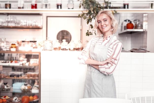 Mulher de negócios bem-sucedida. mulher bonita e confiante em pé com as mãos cruzadas enquanto trabalhava em sua padaria