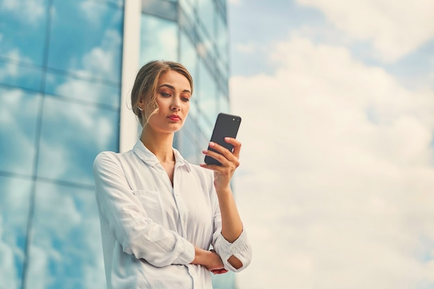 Mulher de negócios bem sucedida mulher de negócios em pé ao ar livre edifício corporativo exterior telefone celular elegância pensativa fofa caucasiana profissional mulher de negócios de meia-idade sonhando com telefone