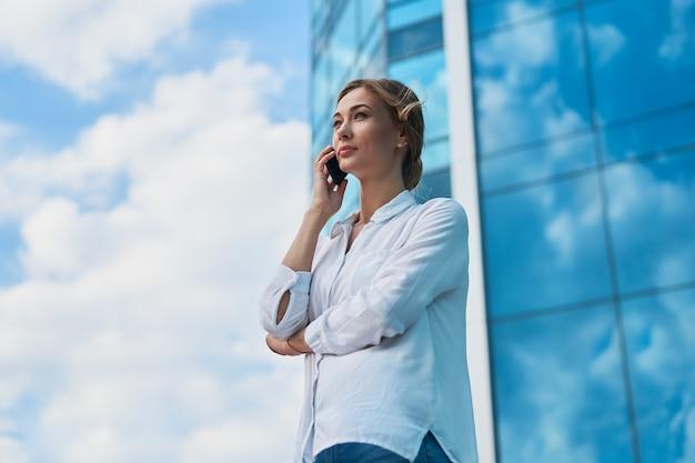 Mulher de negócios bem sucedida mulher de negócios em pé exterior de edifício corporativo ao ar livre. mulher de negócios profissional caucasiana, pensativa, de meia-idade