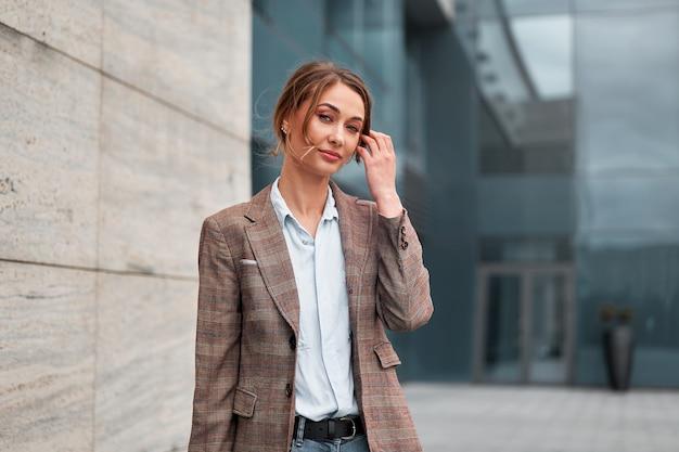 Mulher de negócios bem sucedida mulher de negócios em pé exterior de edifício corporativo ao ar livre. mulher de negócios profissional de confiança caucasiana de meia-idade pensiv