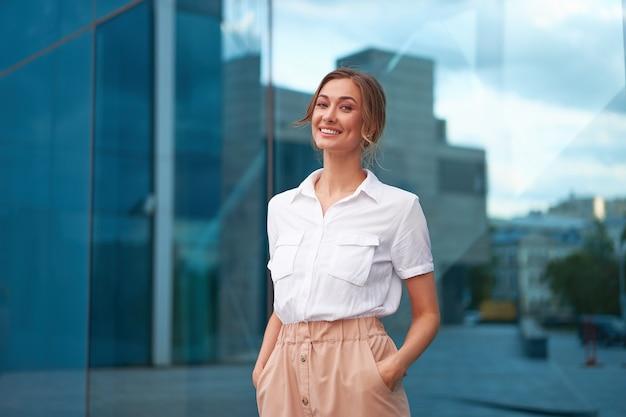 Mulher de negócios bem sucedida mulher de negócios em pé exterior de edifício corporativo ao ar livre. sorriso feliz, caucasiano, confiança, profissional, mulher de negócios, meia-idade