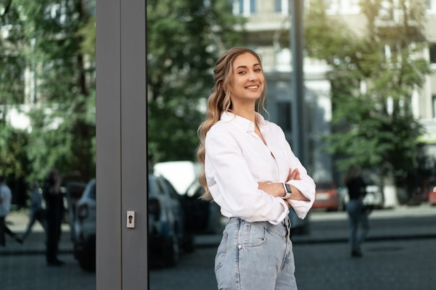 Mulher de negócios bem sucedida mulher de negócios sorridente pessoa de negócios ao ar livre exterior do edifício corporativo feliz caucasiano confiante mulher de negócios profissional meia-idade feminina camisa branca grande janela magra