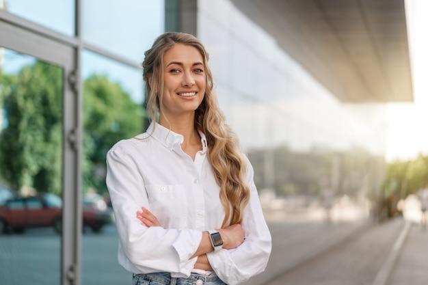 Mulher de negócios bem sucedida mulher sorridente empresário em pé exterior de edifício corporativo ao ar livre. feliz caucasiana confiança profissional mulher de negócios meia idade feminina camisa branca grande janela