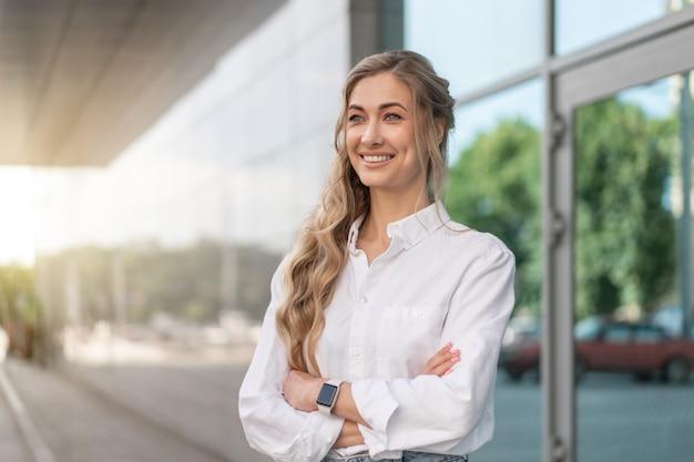 Mulher de negócios bem sucedida mulher sorridente empresário em pé exterior de edifício corporativo ao ar livre. feliz caucasiana, confiante, profissional, mulher de negócios, meia-idade, feminino, branca, camisa, janela grande