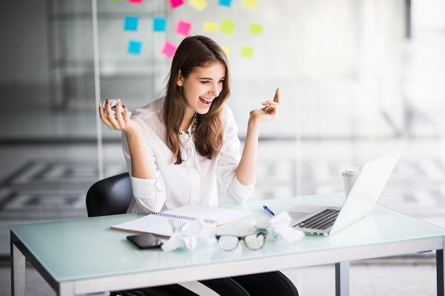 Mulher de negócios bem-sucedida trabalhando em um laptop em seu escritório, vestida com roupas brancas