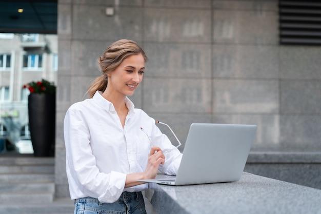 Mulher de negócios bem-sucedida usando laptop pessoa de negócios ao ar livre exterior do edifício corporativo confiança caucasiana mulher de negócios profissional meia-idade com tecnologia de notebook conceito