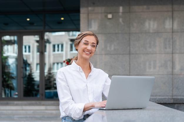Mulher de negócios bem-sucedida usando laptop pessoa de negócios ao ar livre exterior do edifício corporativo confiança caucasiano mulher de negócios profissional meia-idade com tecnologia de notebook conceito