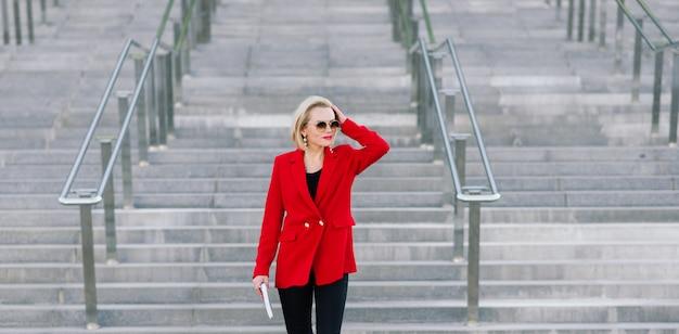 Mulher de negócios bem sucedido com casaco vermelho, falando no smartphone, negociando um acordo sobre o fundo de edifícios altos no centro de negócios.