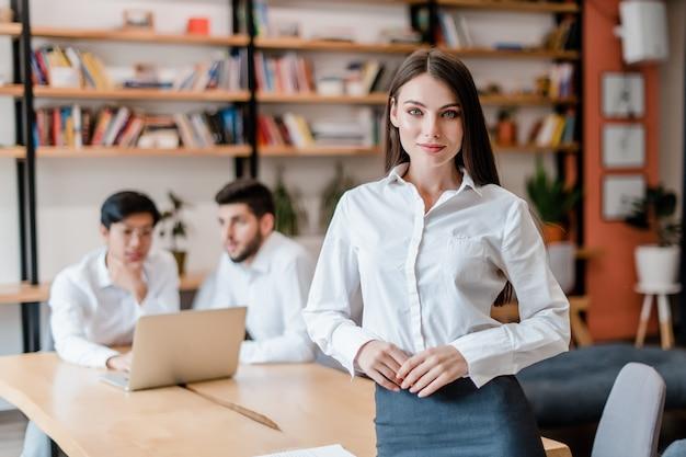 Mulher de negócios bem sucedido jovem trabalhando no escritório da empresa com diversos trabalhadores