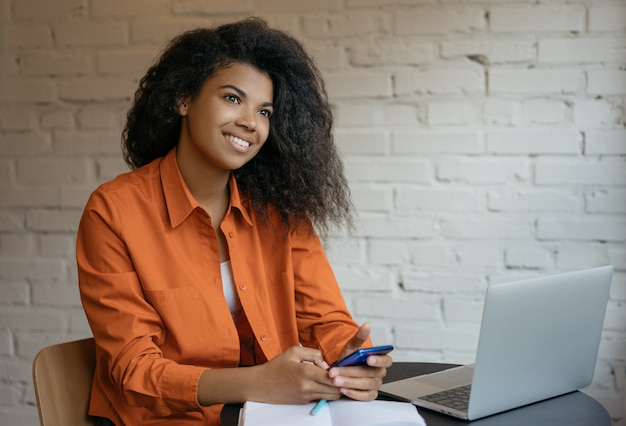 Mulher de negócios bem sucedido, segurando o smartphone, planejando a inicialização no escritório