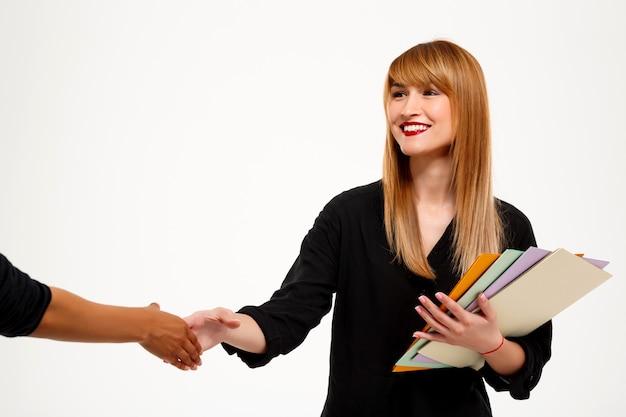 Mulher de negócios bem sucedido segurando pastas aperto de mão saudação sobre parede branca