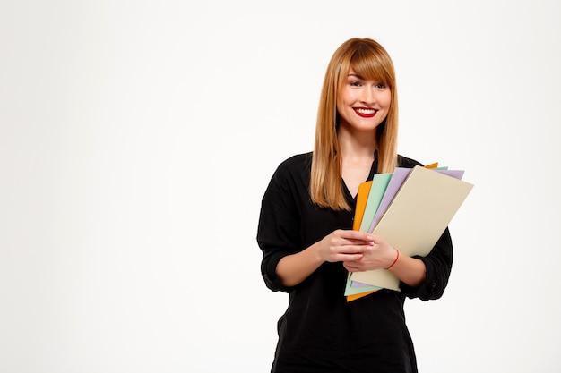Mulher de negócios bem sucedido segurando pastas e sorrindo sobre parede branca