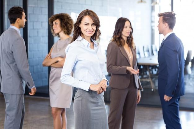 Mulher de negócios bem sucedido sorrindo enquanto seus colegas interagindo uns com os outros