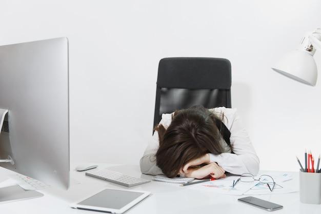 Mulher de negócios bonita, cansada, perplexa e estressada, de cabelos castanhos de terno e óculos dormindo na mesa depois de trabalhar no computador contemporâneo com documentos em um escritório leve