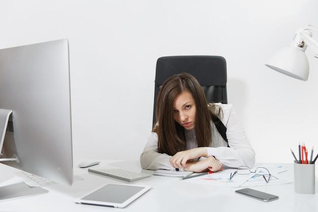 Mulher de negócios bonita, cansada, perplexa e estressada, de cabelos castanhos, de terno e óculos, sentada à mesa, trabalhando em um computador contemporâneo com documentos e monitor em um escritório leve
