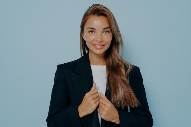 Mulher de negócios bonita caucasiana com expressão facial de satisfação, sorriso encantador, vestida com um elegante terno formal preto, sinceramente olhando para a câmera sobre fundo azul claro. conceito de mulheres bem-sucedidas
