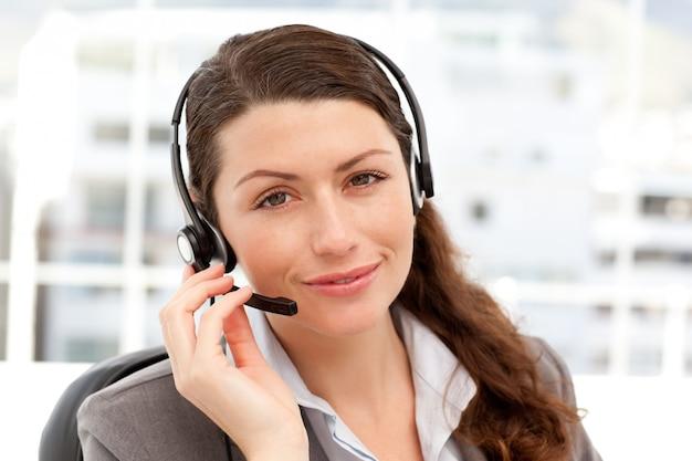Mulher de negócios bonita com fone de ouvido e olhando para a câmera