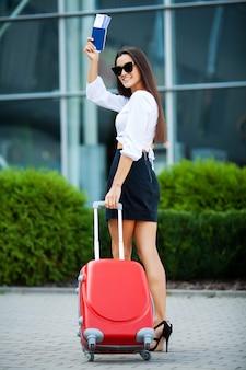 Mulher de negócios bonita com mala vermelha perto do aeroporto