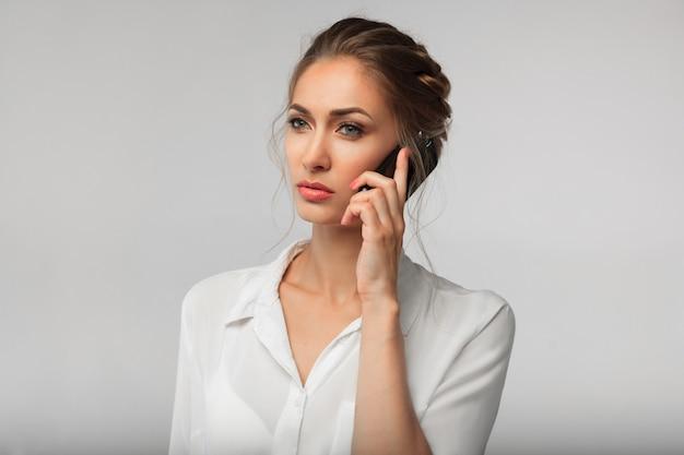 Mulher de negócios bonita com um telefone celular nas mãos. conversa séria. retrato de negócios