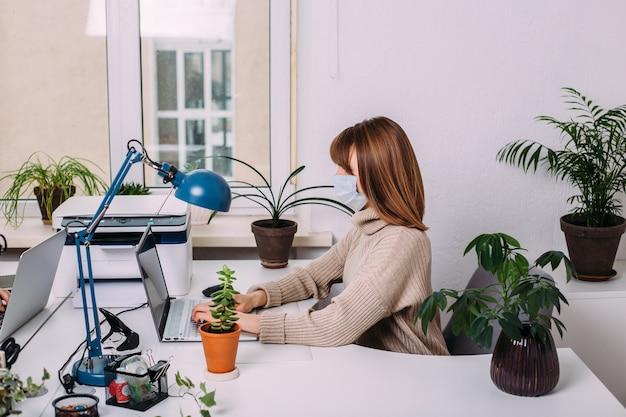 Mulher de negócios bonita com uma máscara protetora médica, trabalhando em um escritório leve, rodeado por plantas. conceito covid-19.